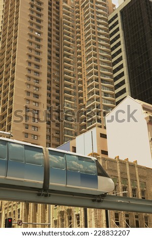 Low angle blurred view of a monorail passing in front of an apartment building - stock photo