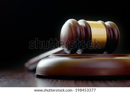 Low-angle close-up of a vintage classical gavel placed on a round sound block, on a wooden table, with copy space on black background - stock photo