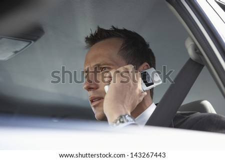 Low angle closeup of serious businessman using mobile phone in car - stock photo