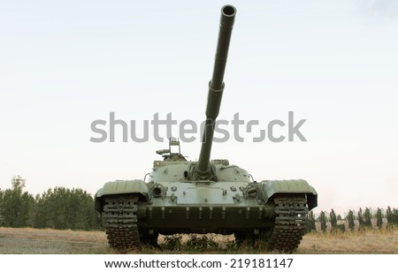 Low angle frontal view of an army tank or armored vehicle with tracks and a cannon extending above the camera parked in a field on display - stock photo