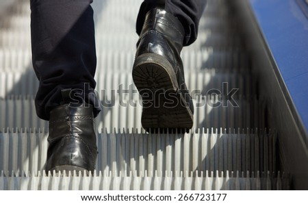 Low angle male feet walking in boots up escalator - stock photo