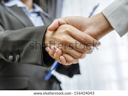 Low angle of businesswomen handshaking - stock photo