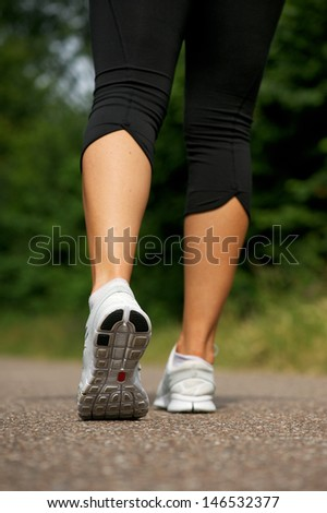 Low angle of young woman walking outdoors in park from behind - stock photo