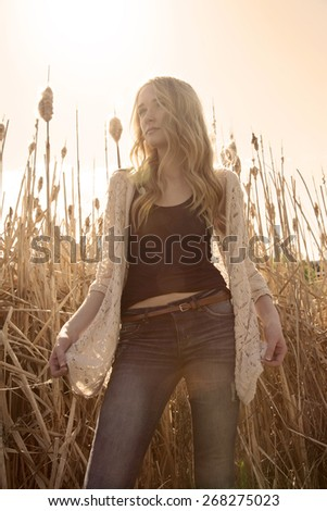 Low angle, outdoor photo of pretty young woman standing in dry grass, backlit, low contrast with warm hues. - stock photo