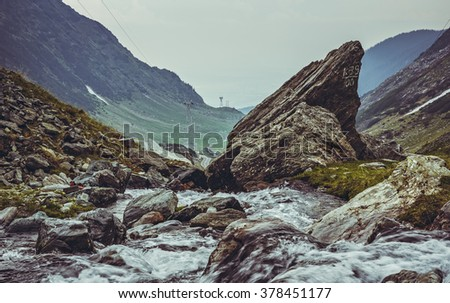Low angle picturesque landscape with mountain stream rapids flowing along the famous meandering Transfagarasan road in Fagaras mountains, Romania - stock photo