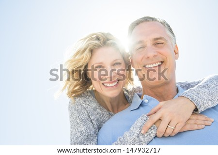 Low angle portrait of cheerful mature woman embracing man from behind against clear sky - stock photo