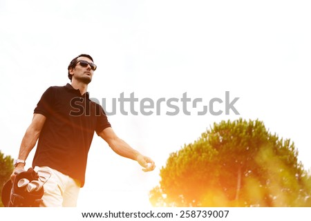 Low angle portrait of professional golf player walking to the next hole holding bag for clubs, good golf game at summer evening weekend on the course, golf player against flare sunset light - stock photo