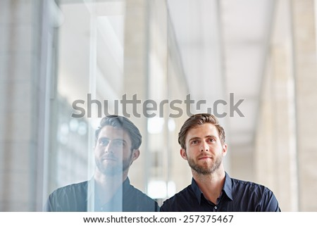 Low angle shot of a handsome executive looking away positively in a modern setting - stock photo