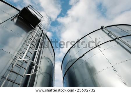 Low-angle shot of ladder and tanks refinery. - stock photo