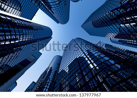 Low angle shot of modern glass city buildings with clear sky background. - stock photo