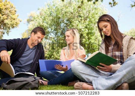 Low angle-shot of three young people working in a park - stock photo