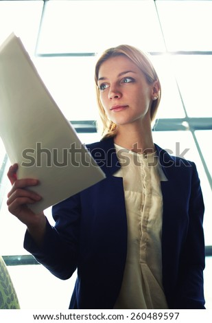 Low angle shot with young attractive businesswoman examining paperwork in bight light office interior sitting next to the window, business woman read some documents before meeting, filtered image - stock photo