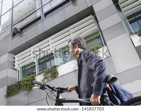 Low angle side view of a businessman carrying bicycle outdoors - stock photo