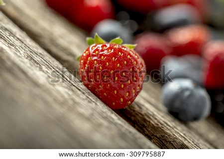 Low angle tilted view of a luscious ripe red strawberry on a rustic wooden table with assorted fresh berries visible in the background. - stock photo