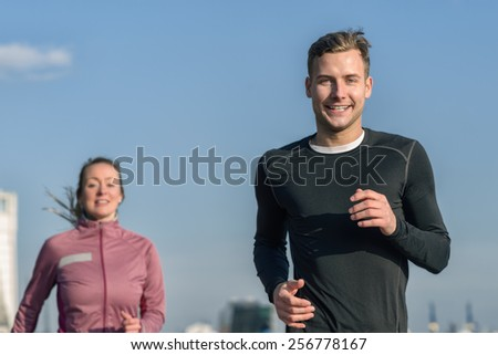 Low angle upper body view against clear blue sky of a smiling handsome man jogging with his wife in a health and fitness concept - stock photo