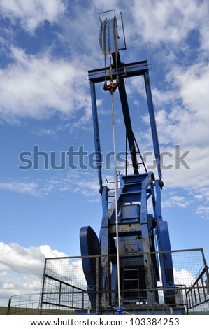 Low-angle vertical closeup of a blue pump jack against the sky, head and rod (bridle) up close - stock photo