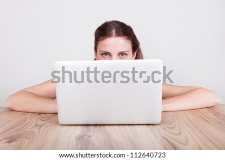 Low angle view across a wooden table of a young woman hiding behind her laptop - stock photo
