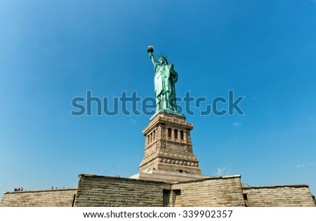Low angle view looking up at the Statue of Liberty, New York on its plinth on Liberty Island an iconic landmark on entering the harbour conceptual of tourism and travel - stock photo