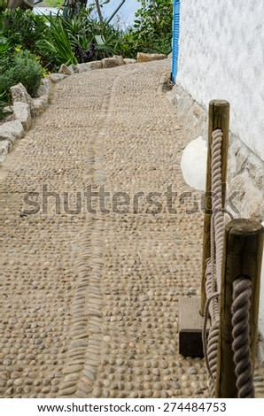 Low Angle View Mediterranean Pebble Cobble Path White Wall and Garden. Vertical. - stock photo