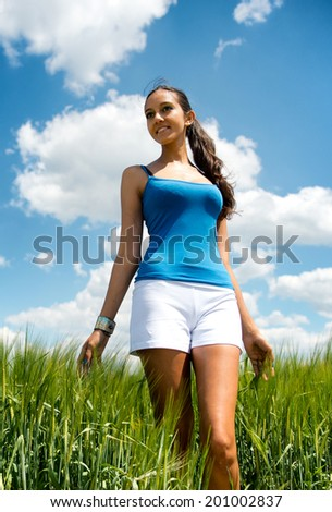 Low angle view of a beautiful tanned shapely young woman in shorts standing in a field of long green grass looking to the side with a lovely smile against a sunny cloudy blue sky - stock photo
