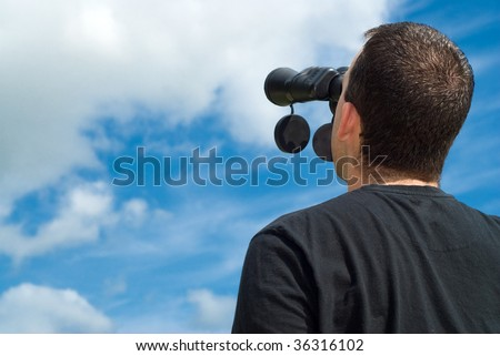 Low angle view of a bird watcher using binoculars with some blue sky and clouds behind him - stock photo