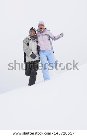 Low angle view of a cheerful couple running down snow covered hill - stock photo