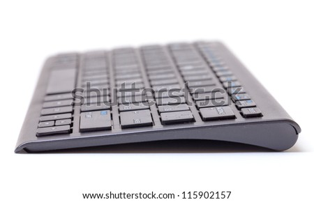 Low angle view of a computer keyboard lying end on the the camera with shallow dof over white - stock photo
