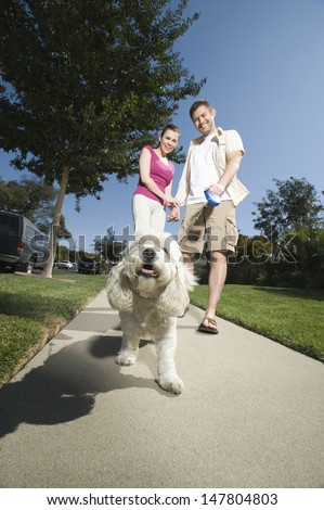 Low angle view of a couple walking dog along pavement - stock photo