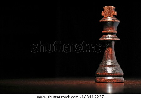 Low angle view of a dark wood king chess piece on a reflective wooden surface against a dark background with copyspace - stock photo