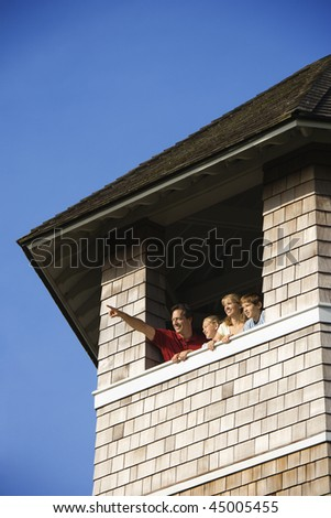 Low angle view of a family looking and pointing out a tower window. Vertical shot. - stock photo