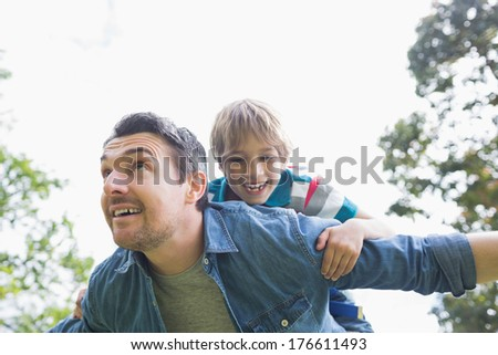 Low angle view of a father carrying cheerful boy on back against the sky - stock photo