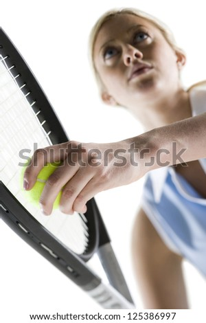 Low angle view of a female tennis player holding ball and racket - stock photo