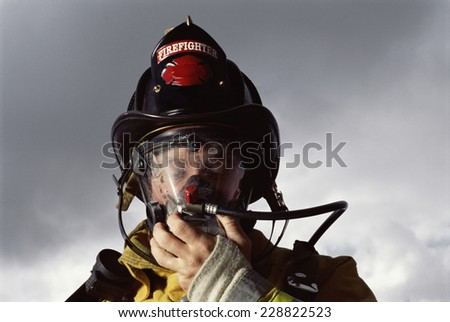 Low angle view of a firefighter in uniform wearing an oxygen mask against cloudy sky - stock photo