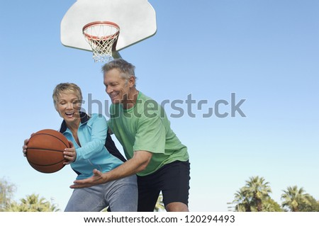 Low angle view of a happy couple playing basketball together at court - stock photo