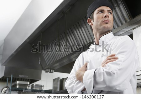 Low angle view of a male chef with arms crossed in kitchen - stock photo