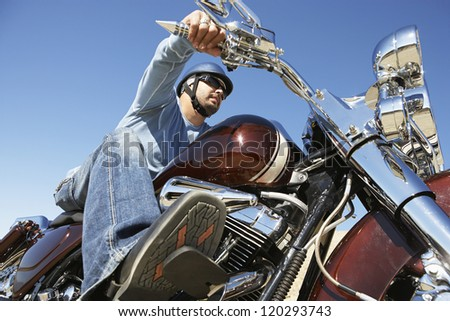 Low angle view of a man riding motorcycle against clear sky - stock photo