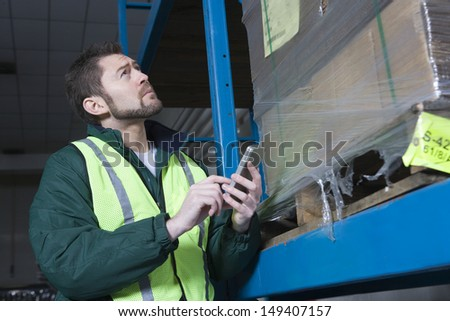Low angle view of a man using calculator in the factory - stock photo