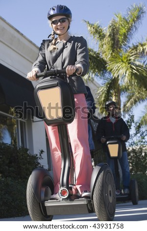Low angle view of a mid adult woman riding a Segway machine - stock photo