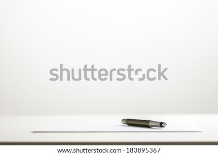 Low angle view of a pen on a sheet of blank white paper on a white desktop with a blank white wall in the background with plenty of copyspace. - stock photo