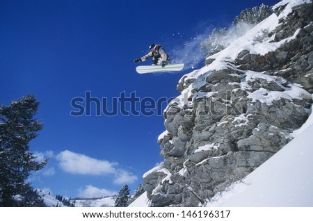 Low angle view of a person on snowboard jumping midair over cliff - stock photo
