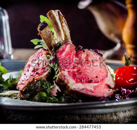 Low angle view of a plate of gourmet rare roasted lamb cutlets with spices and seasoning served on a fresh herb salad for a healthy rustic dinner - stock photo