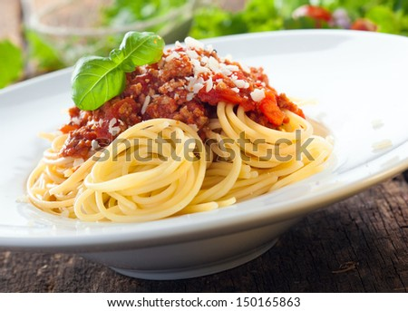 Low angle view of a serving of Italian spaghetti with a meat based bolognese, or bolognaise, sauce on a plain white plate - stock photo