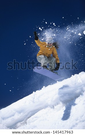 Low angle view of a snowboarder in midair above ski slope with snow powder trailing behind - stock photo