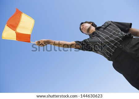 Low angle view of a soccer linesman waving flag against clear blue sky - stock photo