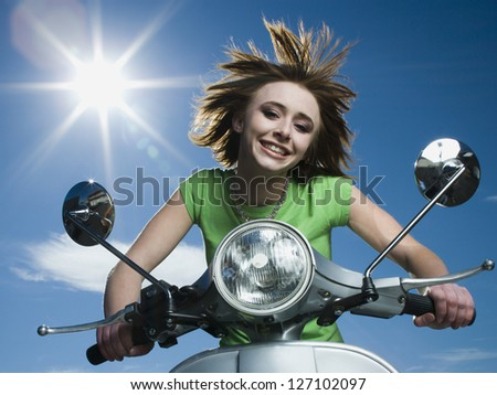 Low angle view of a teenage girl riding a scooter - stock photo