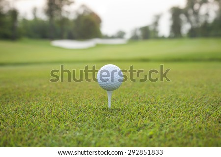 Low angle view of a white golf ball on a tee with defocused background - stock photo