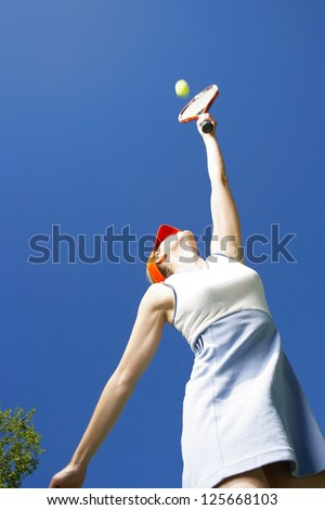 Low angle view of a woman stretching up to the ball with her racquet while serving - stock photo