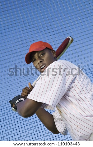 Low angle view of a young baseball player batting against net - stock photo
