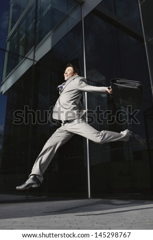 Low angle view of a young businessman with briefcase jumping outside office building - stock photo