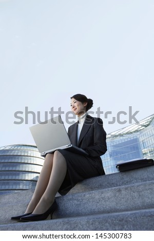 Low angle view of a young businesswoman using laptop on outdoor steps - stock photo